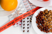 Top view of ribbon with allergy lettering, pills and nuts on table