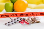 Stuha s alergií písmo v blízkosti pilulky a ovoce na rozmazaném pozadí