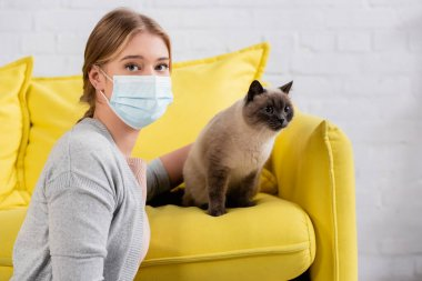 Young woman in medical mask looking at camera near siamese cat at home stock vector