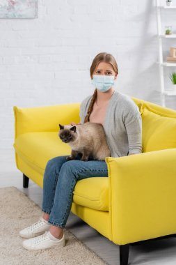 Displeased woman in medical mask looking at camera during allergy near furry siamese cat on sofa stock vector
