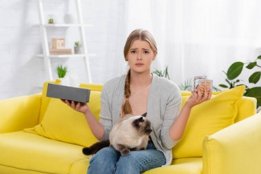 Displeased woman with allergy holding pills and box with napkin near siamese cat stock vector