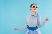 šťastná žena v slunečních brýlích a elegantní oblečení stojící izolované na modré