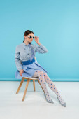 extravagant woman touching sunglasses while sitting on blue background