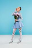 šťastná stylová žena drží růžové chryzantémy, zatímco stojí se zavřenýma očima na modrém pozadí