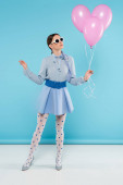 extravagant woman in dotted tights and sunglasses posing with pink balloons on blue background