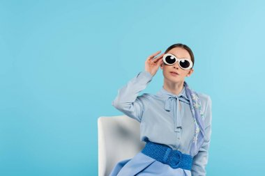 Glamour woman touching sunglasses while sitting on chair isolated on blue stock vector