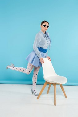 Glamour woman in sunglasses and polka dot tights posing near chair on blue background stock vector