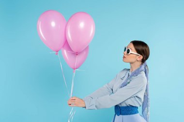 Young woman in stylish clothes and sunglasses holding pink balloons isolated on blue stock vector