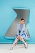 elegantní žena dívá na kameru, zatímco sedí v blízkosti otvoru v modrém papíru na šedém pozadí