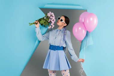 Stylish woman posing with pink flowers and balloons near blue ripped paper on grey background stock vector