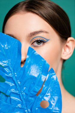Portrait of young woman obscuring face with blue wet leaf isolated on green stock vector