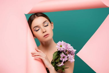 Pretty woman with closed eyes near chrysanthemums and pink torn paper isolated on green stock vector