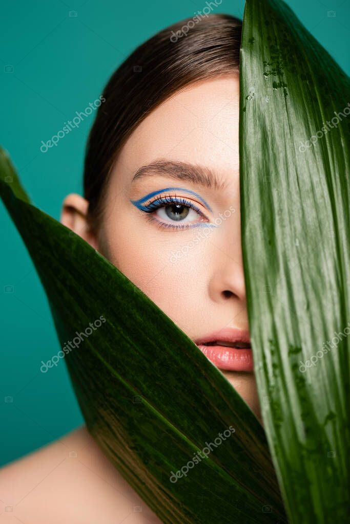 Sensual woman looking at camera near glossy leaves isolated on green stock vector