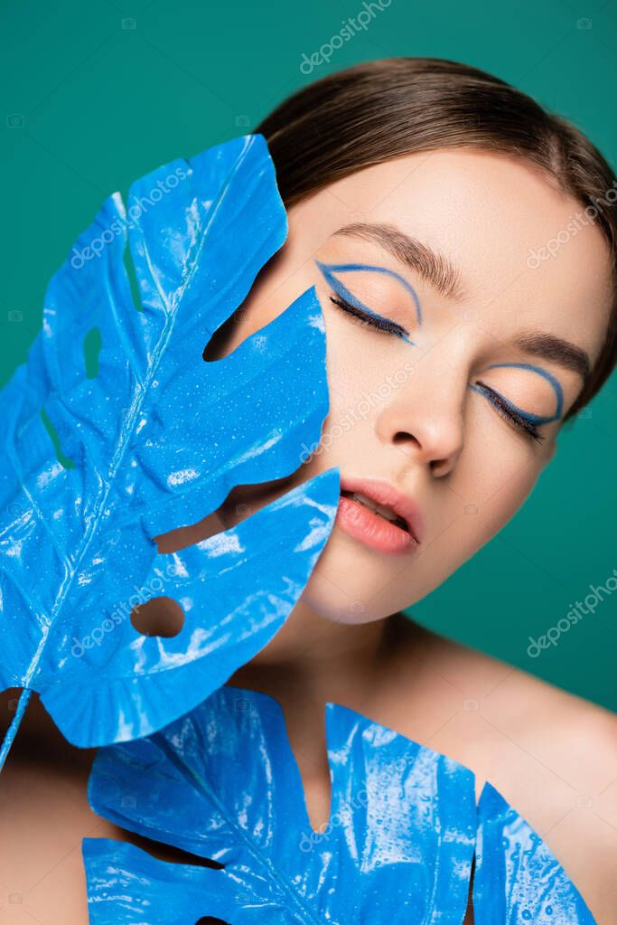 Portrait of young charming woman near blue glossy leaves isolated on green stock vector