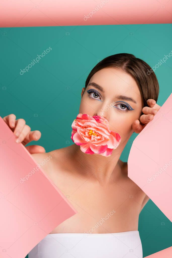 Pretty woman with peony flower in mouth looking at camera near hole in pink paper  isolated on green stock vector