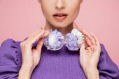 částečný pohled na ženu v purpurové blůze držící brýle s květy izolované na růžové