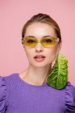 Young woman in colored eyeglasses and fresh lettuce earring isolated on pink stock vector