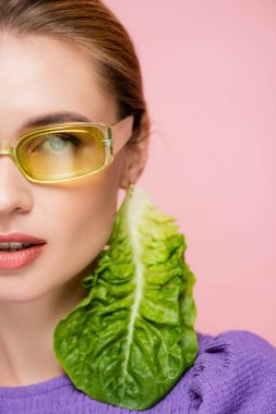 Close up view of young woman in colored eyeglasses, with fresh lettuce earring isolated on pink stock vector
