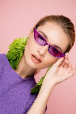 Stylish woman in earrings made of fresh lettuce, touching purple eyeglasses isolated on pink stock vector