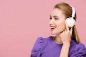 örömteli nő megérinti gomba fülhallgató elszigetelt rózsaszín
