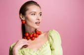 érzéki nő piros cseresznye paradicsom nyaklánc néz el elszigetelt rózsaszín