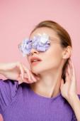 smyslná žena s květinami v brýlích pózovat izolované na růžové