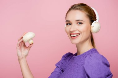 young woman with mushroom in headphones smiling at camera isolated on pink