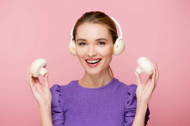 smiling woman with mushrooms in headphones holding champignons isolated on pink