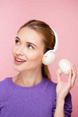 cheerful woman with mushroom in headphones looking away isolated on pink