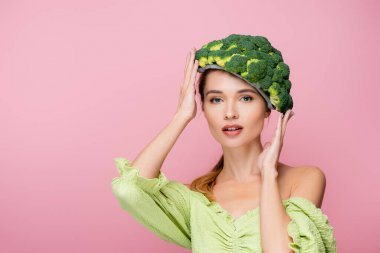 Pretty woman touching hat made of fresh broccoli isolated on pink, surrealism concept stock vector