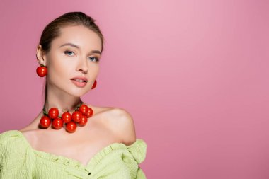 Pretty woman in green blouse and necklace made of cherry tomatoes isolated on pink stock vector