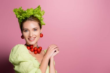 Smiling woman in hat, necklace and earrings made of vegetables posing on pink stock vector