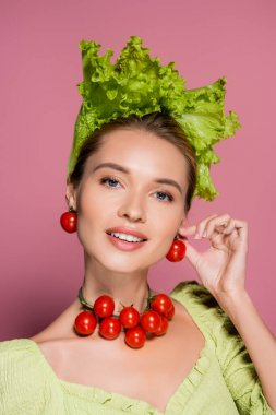 Smiling woman in hat, necklace and earrings made of fresh vegetables posing on pink stock vector