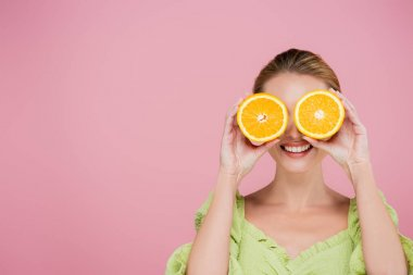 Smiling woman covering eyes with halves of ripe orange isolated on pink stock vector