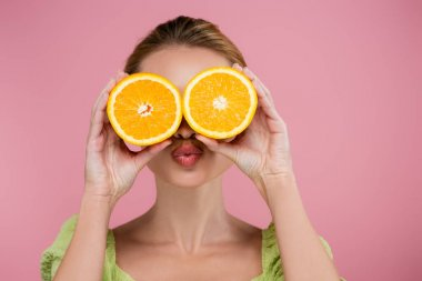 Young woman sending air kiss while covering eyes with orange halves isolated on pink stock vector