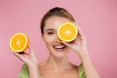 Cheerful woman covering eye with half of ripe orange isolated on pink stock vector