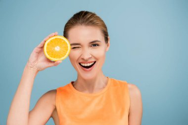 Excited woman winking at camera while holding half of ripe orange isolated on blue stock vector
