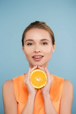 Smiling woman with natural makeup holding half of ripe orange isolated on blue stock vector