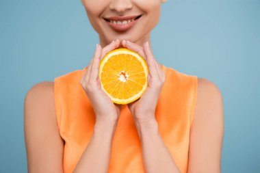 Cropped view of smiling woman with half of ripe orange isolated on blue stock vector