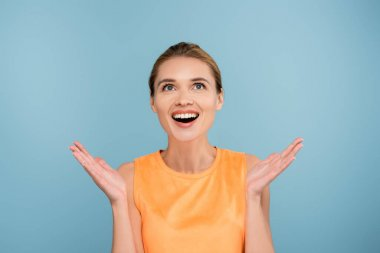 Astonished woman with open arms looking up isolated on blue stock vector