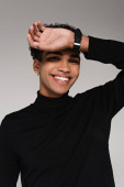 gepiercter afrikanisch-amerikanischer Mann im Rollkragenpullover lächelt isoliert auf grau