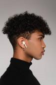 Seitenansicht eines afrikanisch-amerikanischen Mannes, der Musik in drahtlosen Kopfhörern isoliert auf grau hört
