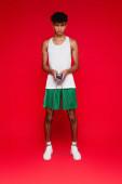 volle Länge des sportlichen afrikanisch-amerikanischen Mannes in Shorts und Tank Top beim Training mit Springseil auf rot