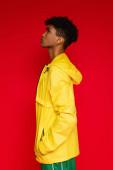 boční pohled na afrického Američana ve žluté bundě pózuje izolované na červené