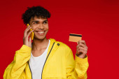 happy african american man in jacket talking on smartphone and holding credit card isolated on red