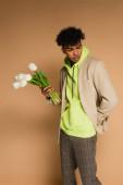 mladý africký Američan v zelené mikině a sako drží tulipány na béžové