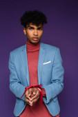 junger afrikanisch-amerikanischer Mann mit gefesselten Händen blickt in die Kamera auf lila