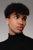 junger afrikanisch-amerikanischer Mann in schwarzem Rollkragenpullover, der isoliert auf grauem Grund wegschaut