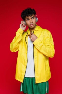 young african american man in yellow jacket listening music in wireless headphones isolated on red