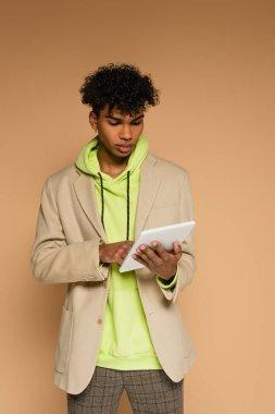 Trendy african american man in hoodie and blazer holding digital tablet on beige stock vector